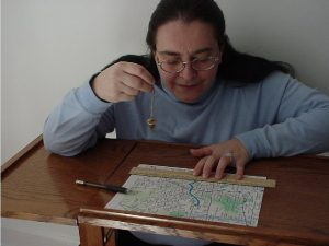 Susan Spuhler, former Boston Chapter Dowsers Board Member demonstrating the map dowsing method.
